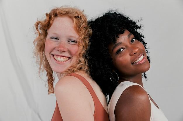 カメラを見て背中合わせに傾いている若い多民族女性の友人の笑顔 無料写真
