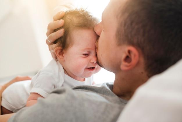 お父さんがおでこに赤ちゃんにキス 無料写真