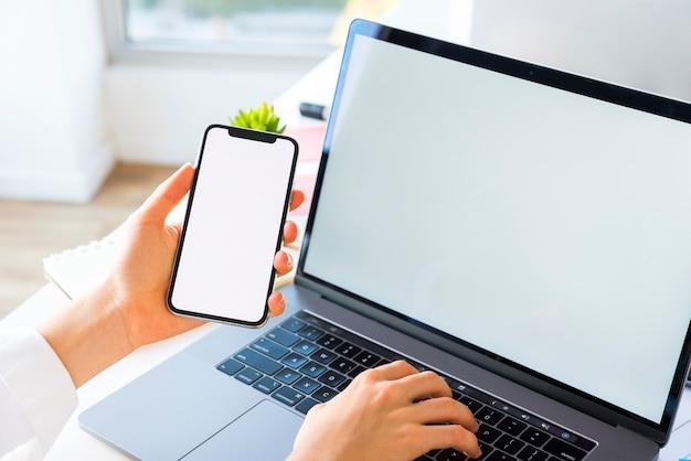 ノートパソコンと携帯電話を持つオフィスのデスクトップ 無料写真