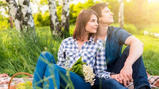 空き地にピクニックで休憩を持つ恋人 無料写真