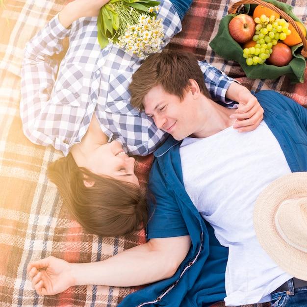 森の毛布の上に横たわる若いカップル 無料写真