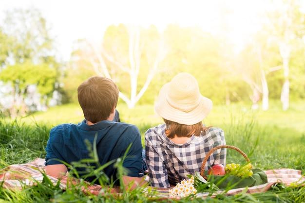 森の格子縞の上に横たわる認識できないカップル 無料写真