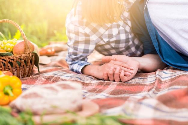 認識できないカップルの毛布の上に横たわると手を繋いでいます。 無料写真