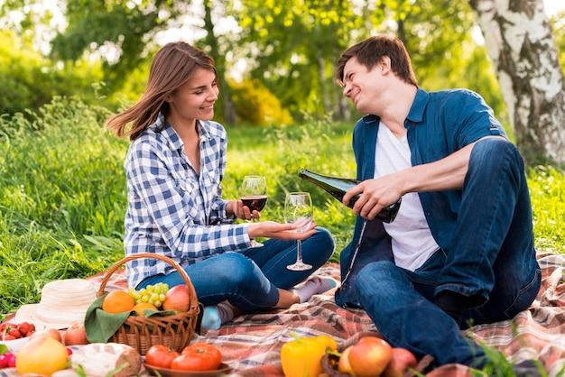 若いカップルが毛布の上に座ってワインを注ぐ 無料写真