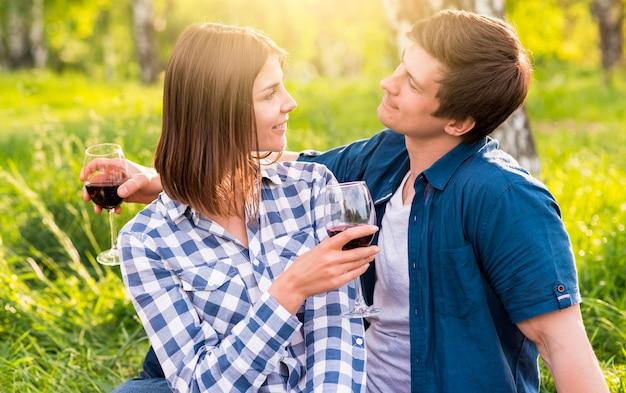 森に座ってお互いを楽しんでいるカップル 無料写真