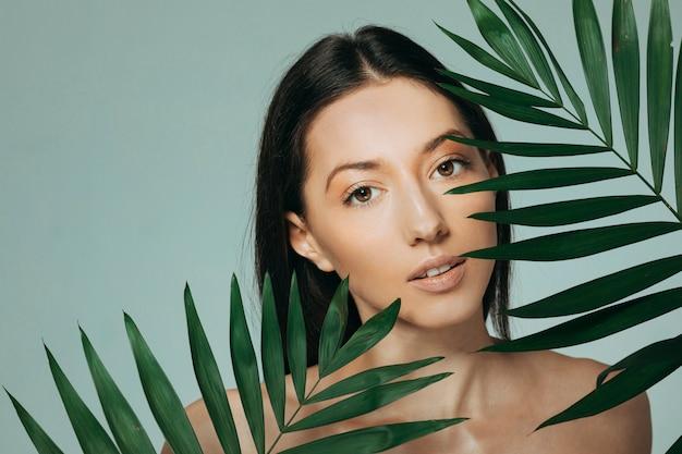 エキゾチックな葉でポーズブルネットの少女 無料写真