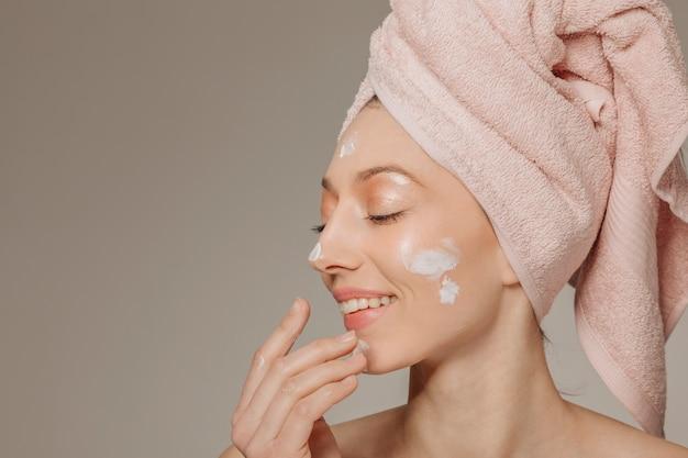 ローションを使用して頭にタオルを持つ少女 無料写真