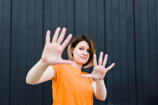 黒い壁に対して停止ジェスチャーを示す若い女性の肖像画 無料写真