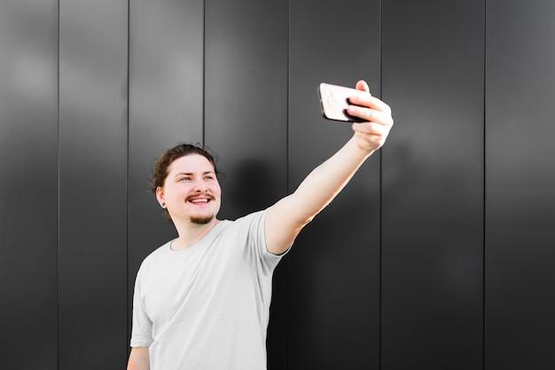 Портрет улыбающегося человека, принимающего селфи на мобильный телефон Бесплатные Фотографии