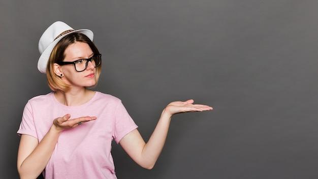 Шляпа молодой женщины нося представляя что-то против серой предпосылки Бесплатные Фотографии