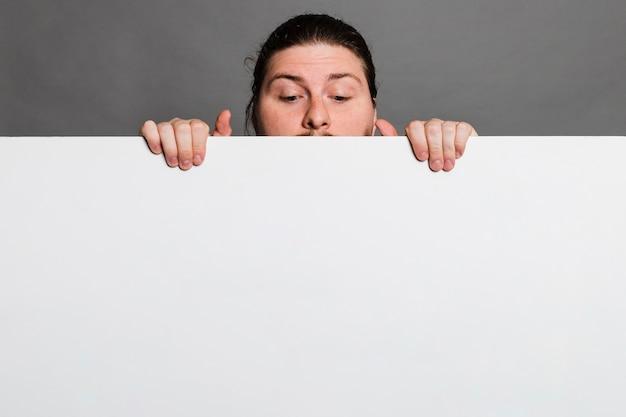 灰色の背景に対して白いカード紙の後ろに覗く男のクローズアップ 無料写真