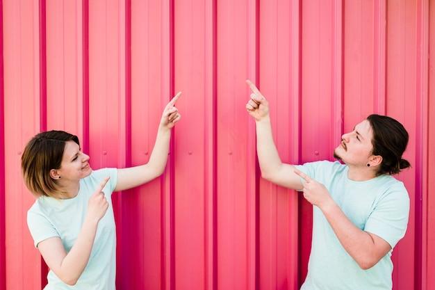 段ボール鉄シートに対して上向きに自分の指を指している若いカップル 無料写真