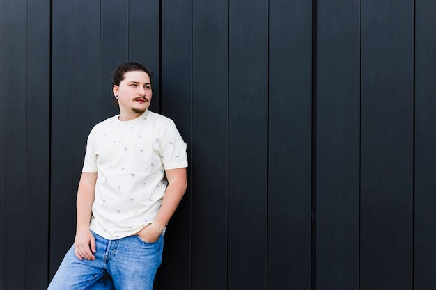 Портрет молодого человека с рукой в кармане, стоя у черной стены Бесплатные Фотографии