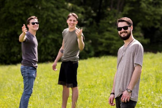 若い男性がピクニックに友達を呼んで 無料写真
