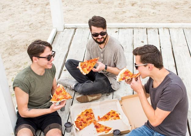 Компания молодых парней ест пиццу на пляже Бесплатные Фотографии