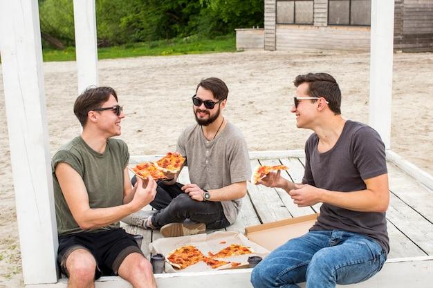 Счастливая компания в чате и едят пиццу на пикник Бесплатные Фотографии