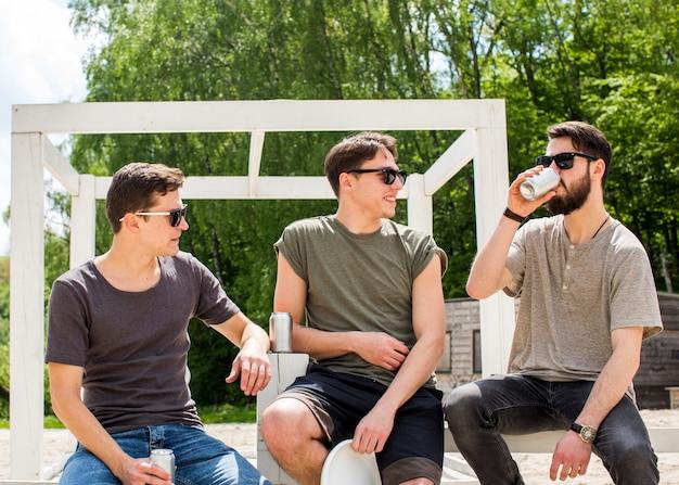 Друзья-мужчины отдыхают с освежающими напитками Бесплатные Фотографии