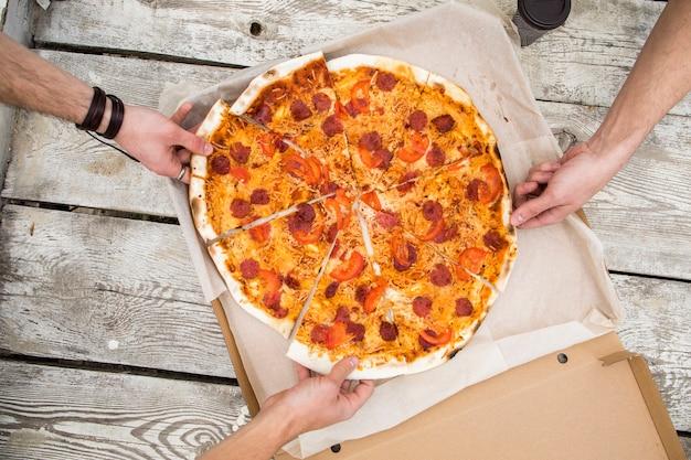ボックスからおいしいピザの部分を取っている人々 無料写真