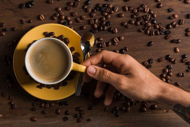 プレートの近くのコーヒーと手持ち株カップ 無料写真