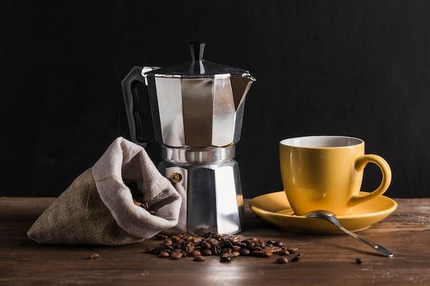 黄色のカップと豆と袋の近くのコーヒーメーカー 無料写真