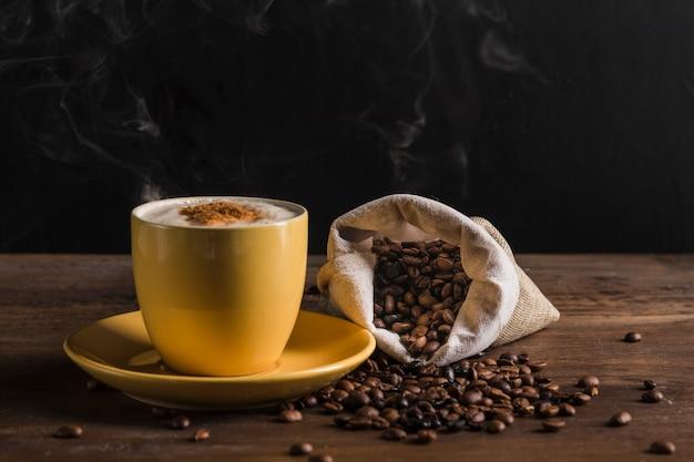 黄色の一杯のコーヒーと豆と袋 無料写真