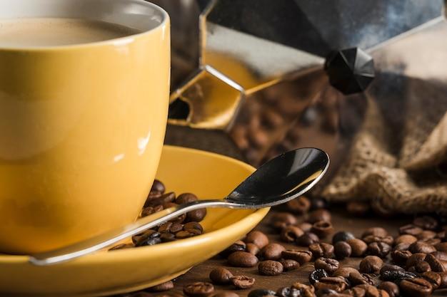 黄色のコーヒー豆と間欠泉のコーヒーメーカーの近くに設定 無料写真