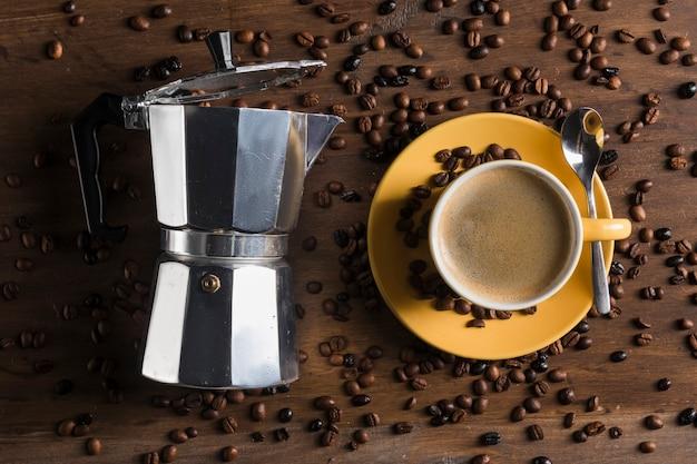 Гейзерная кофеварка возле желтой чашки с ложкой и тарелкой Бесплатные Фотографии