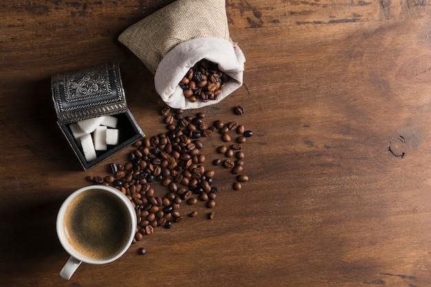 砂糖とカップのボックスの近くのコーヒー豆の袋 無料写真