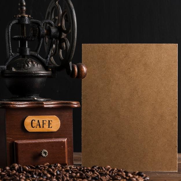Картон и винтажная кофемолка возле бобов Бесплатные Фотографии