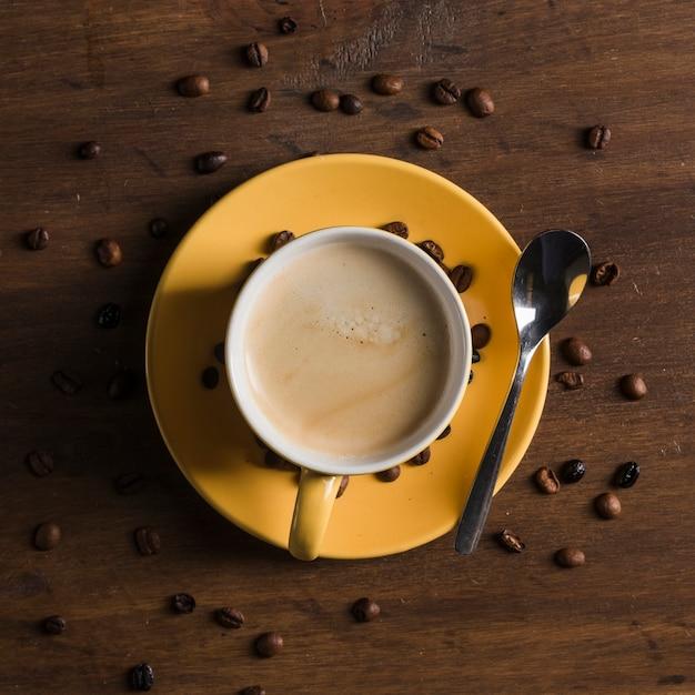 コーヒー豆の近くの飲み物と黄色のカップ 無料写真