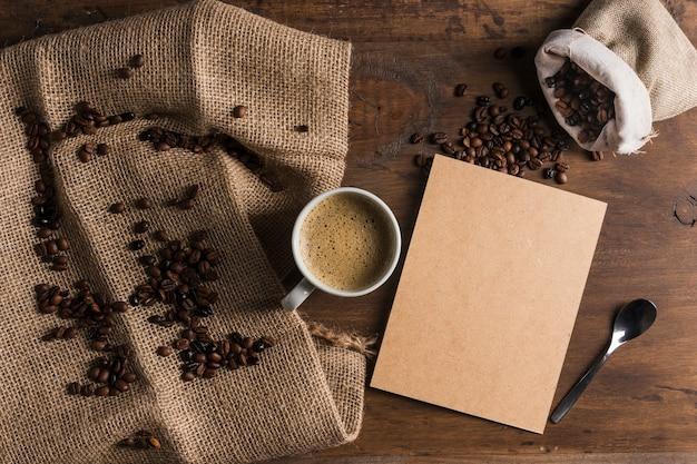 コーヒー豆と荒布と袋の近くの段ボールとカップ 無料写真