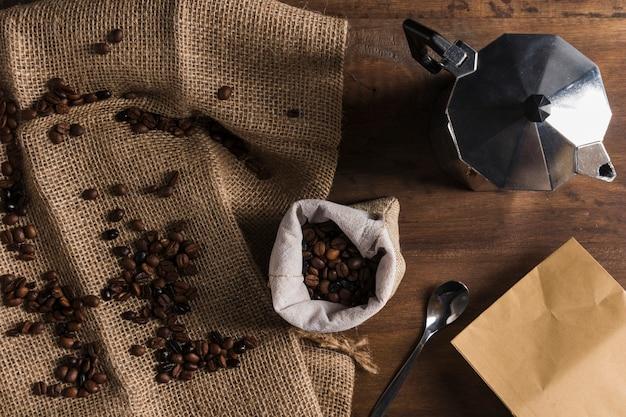 袋、コーヒーメーカー、パッケージの近くの荒布を着たコーヒー豆の散在 無料写真