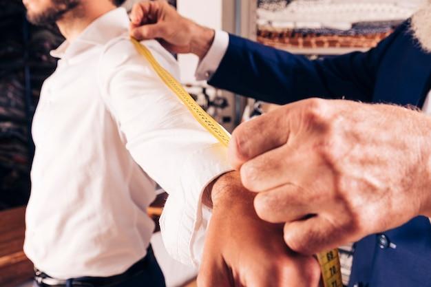 ワークショップで男性のファッションデザイナーが袖を測る 無料写真