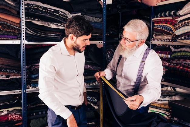 年配の男性が店で顧客に布の測定を行います 無料写真