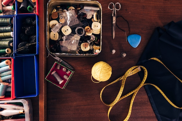 ミシン糸スプール。ボタンウールボール巻き尺;チョーク;布と木製のテーブルの上のはさみ 無料写真