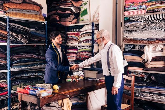 彼のワークショップで若い男性の仕立て屋と握手シニア男性の顧客 無料写真