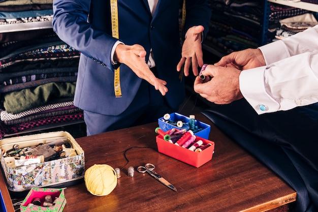 店で男性の仕立て屋に糸のスプールを示す顧客の手のクローズアップ 無料写真