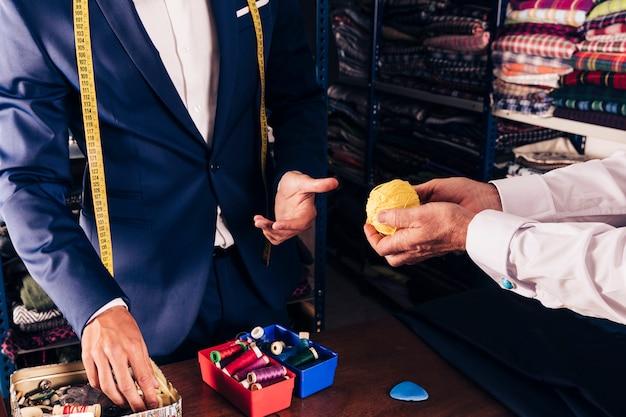店で男性のファッション・デザイナーに黄色のウールボールを示す顧客の手 無料写真