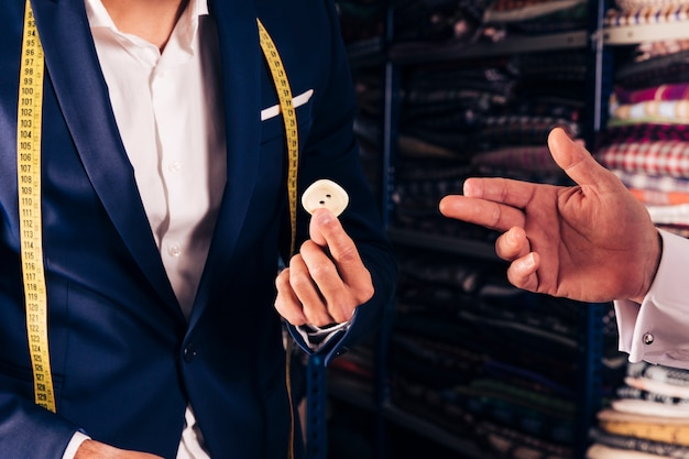 彼の店で身振りで示す彼の顧客に男性の仕立て屋表示ボタンのクローズアップ 無料写真