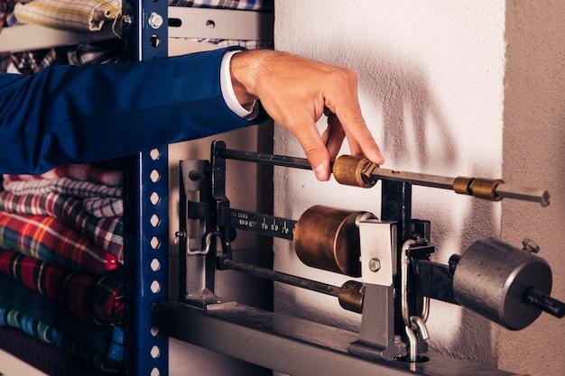 ファブリック計量スケール機を調整する男性ファッション・デザイナーのクローズアップ 無料写真