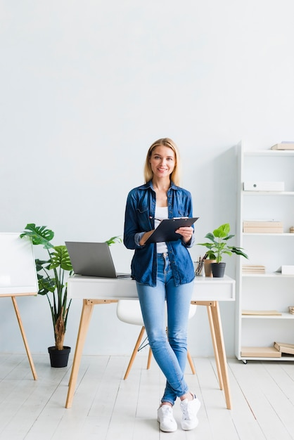タブレットをキャビネットで立っている若い女性 無料写真