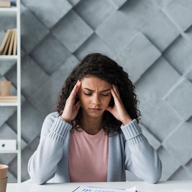 頭痛に苦しんでいる若い女性 無料写真