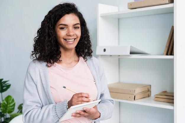 Счастливая молодая женщина с блокнотом в офисе Бесплатные Фотографии