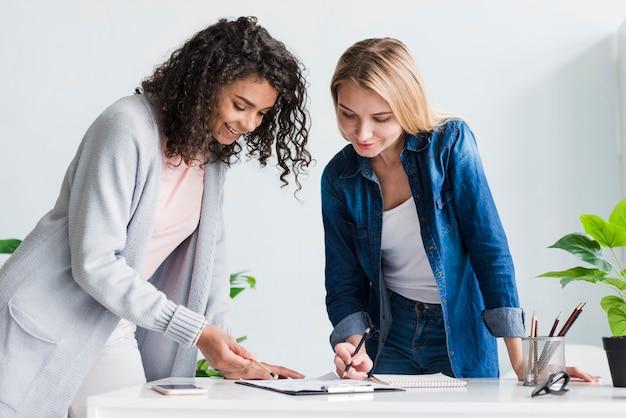 プロジェクトを議論する机の上にもたれて女性の同僚 無料写真