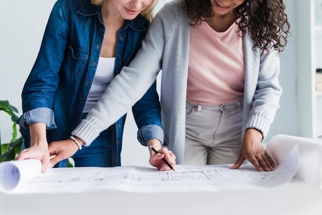 フロアプランで一緒に働く女性エンジニア 無料写真
