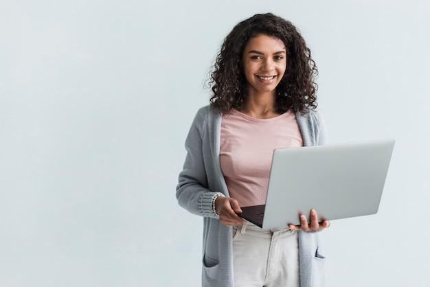 灰色のラップトップを持つ民族女性の笑みを浮かべてください。 無料写真