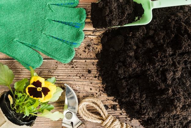 Цветочный горшок с анютиными глазками; садовые инструменты и перчатки с плодородной почвой на деревянный стол Бесплатные Фотографии