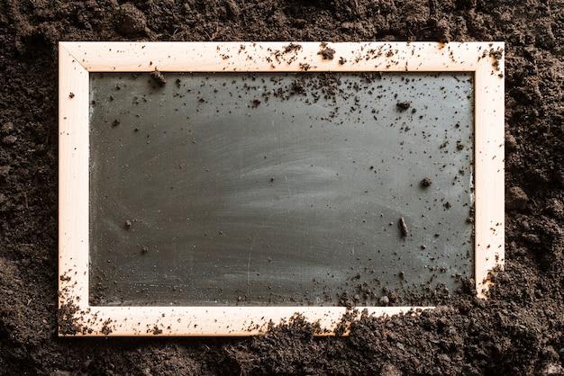 土の上の空白の木製スレート 無料写真