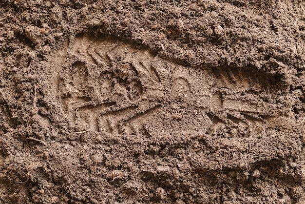 ソールの靴を土に刻印 無料写真