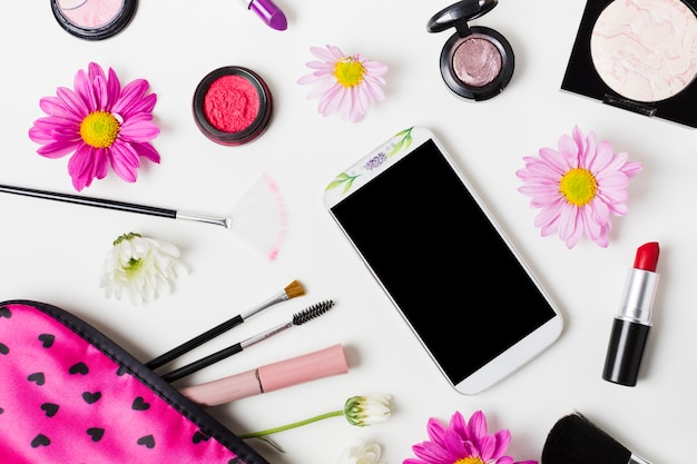 スマートフォンとライトテーブルの上の装飾的な化粧品 無料写真